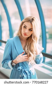 Beautiful young business woman in business dress blue suit with long blonde hair. Modern business fashion street style