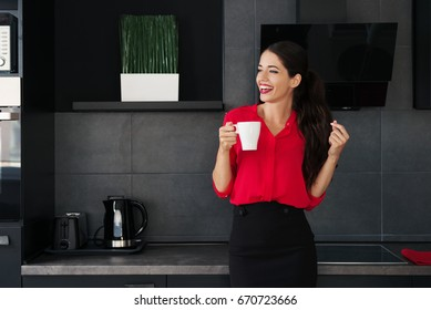 Beautiful young business woman drinking coffee/tea in a modern kitchen