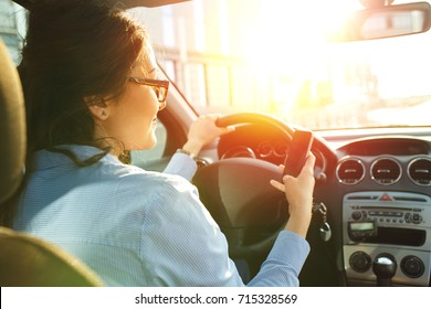Beautiful young business woman driving a car and looking at phone.