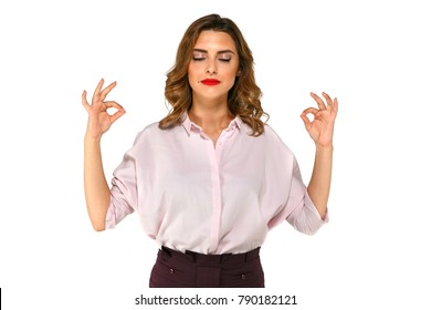 Beautiful young business woman meditates, trying to calm down after work, dressed in office clothes, with red lipstick. Isolated on white background.