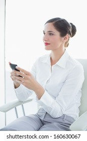Beautiful young business woman with mobile phone looking away