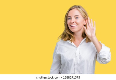 Beautiful young business woman over isolated background smiling with hand over ear listening an hearing to rumor or gossip. Deafness concept.