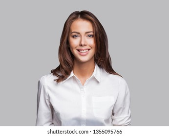 Beautiful young business woman portrait. Smiling cute girl with long hair studio shot. Isolated on gray background