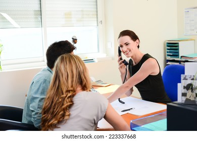 beautiful young business woman in selling transaction with happy young couple in office