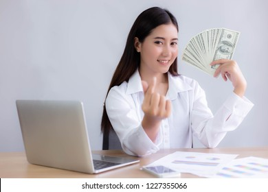 Beautiful young business woman is showing money and using hand making a little of heart. Charming beautiful woman can earn a lot of money. Attractive asian woman gets happy with smile face with laptop