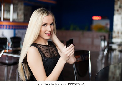 Beautiful young business woman smiling with mobile phone in cafe
