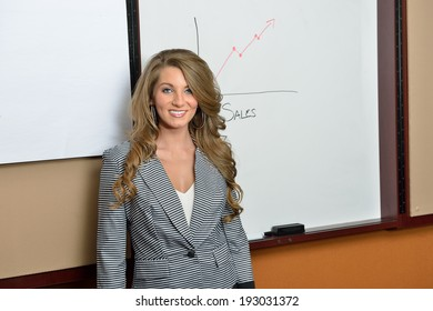 Beautiful young business woman standing in grey and black pants suit in front of conference room dry erase board showing increasing sales