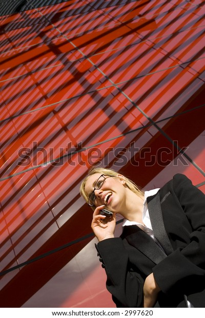 A beautiful young business woman talking on her phone in front of a hi tech office building