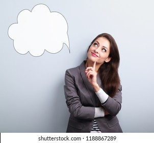 Beautiful young business woman thinking and looking up on balloon cloud above on blue background