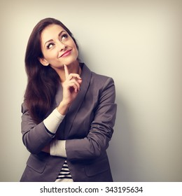 Beautiful young business woman thinking and looking up with finger under the face. Toned closeup portrait