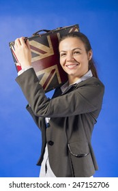 Beautiful young business woman with vintage suitcase on shoulder smiling looking at the camera, on blue background, studio shot. Work and travel concept