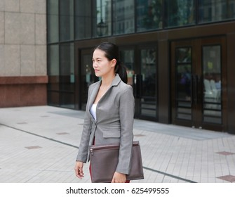 Beautiful young business woman walking outside. Asian businesswoman office worker in downtown business district.