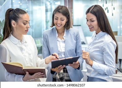 Beautiful young business women working together on contract documents.