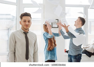 beautiful young businessman with his successful team. A group of freelancers successfully concluded the contract. Success in work. Happy managers and boss. Throw sheets of paper into the air. Day off