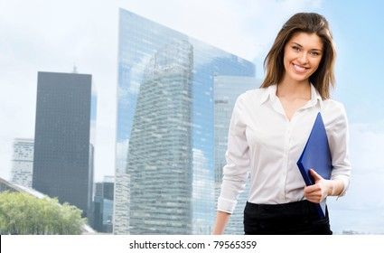 Beautiful young businesswoman among the skyscrapers of the modern business center