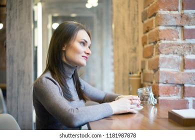Beautiful young businesswoman in the cafe, using digital tablet and drinking coffee smiling