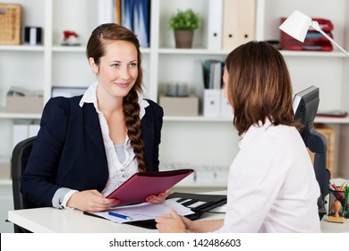 Beautiful young businesswoman conducting a job interview seated at her desk in her office holding a folder and smiling at the potential female candidate