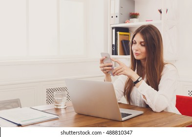 Beautiful young businesswoman dial at mobile phone, sitting at wooden desk with laptop and red cup. Modern office worker in white room. Succesfull woman, female carreer concept.