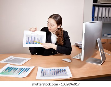 Beautiful young businesswoman with financial reports at the office