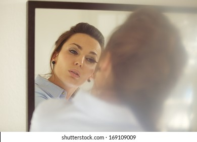 Beautiful young businesswoman putting on mascara while looking at the mirror. Caucasian female model putting makeup getting ready for work.