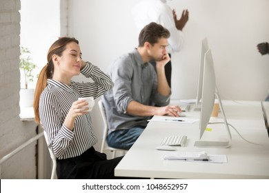 Beautiful young businesswoman relaxing during break at work in office holding cup of coffee in hand, happy calm employee enjoying pleasant stress free morning in front of computer at workplace