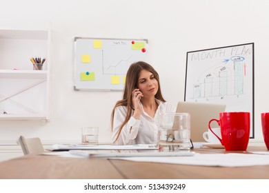 Beautiful young businesswoman sitting by wooden desk with laptop. Modern office worker in white room interior. Succesfull woman, female carreer concept.