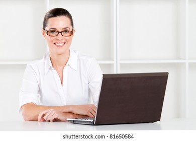 beautiful young businesswoman sitting in office with laptop