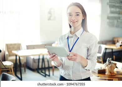 Beautiful young businesswoman smiling at camera at business event, tablet computer in her hands and blank id card around her neck