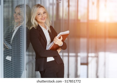 beautiful young businesswoman smiling and standing with folder in the office. looking at camera. copy space.
