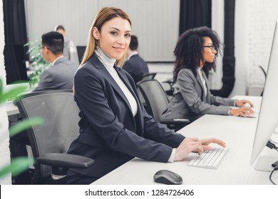 beautiful young businesswoman using desktop computer and smiling at camera in office