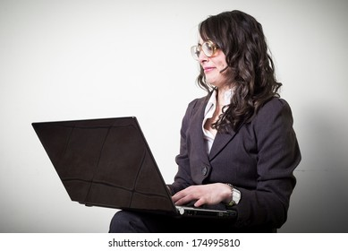 beautiful young businesswoman using notebook on gray background