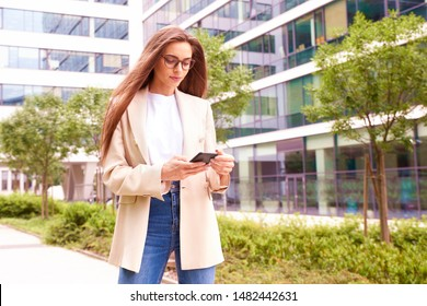 Beautiful young businesswoman walking on the street and text messaging.
