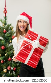 Beautiful young businesswoman wearing santa hat and holding Christmas gifts.