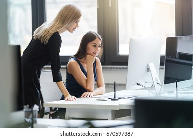 Beautiful young bussines women working together in the office on a computer