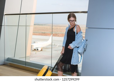 Beautiful young casual Caucasian woman at the airport with a yellow suitcase and blue backpack goes on a journey.