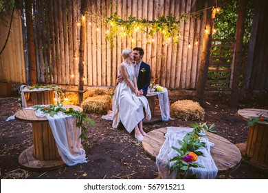 Beautiful young casual couple in love, sitting at wooden table. Wedding location is at country style garden with American lighting and simple trend decor