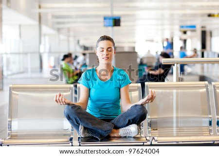 beautiful young casual woman doing yoga meditation at airport
