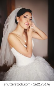 Beautiful young caucasian bride is getting ready at home.