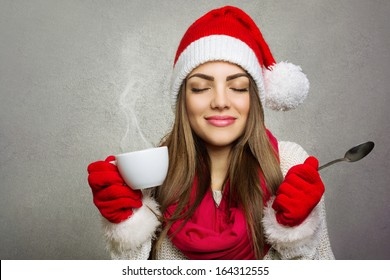 Beautiful young Caucasian brunette woman holding a cup of hot coffee and spoon smiling with eyes closed wearing Santa beanie hat against gray wall texture background. Copy space available.
