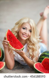 Beautiful young caucasian brunette woman holding a watermelon slice. Healthy food and happy summer holiday concept. Slice of summer goodness. Beautiful young woman holding slice of watermelon