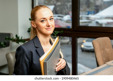 Beautiful young caucasian businesswoman holding a folder with documents sitting at the table in office or cafe