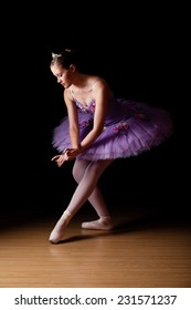 Beautiful young Caucasian female ballet dancer wearing lilac tutu against black backdrop in studio