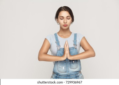 Beautiful young caucasian  female, holding hands in namaste or prayer, keeping eyes closed while practicing yoga and meditating at home alone. Studio shot on gray background.