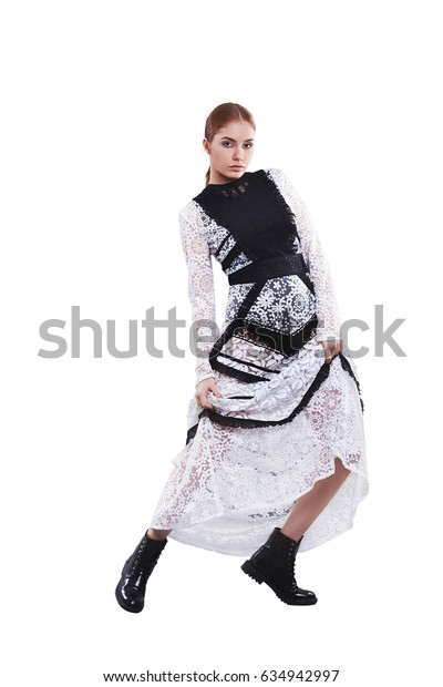 Beautiful young caucasian girl in long lace black and white evening dress isolated on white