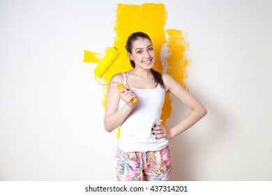 Beautiful young caucasian model in coloured shorts and white shirt and posing holding outrigger in her hands, painting the wall and looking at camera. Studio shot.