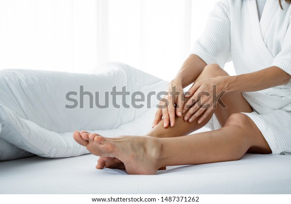 Beautiful young Caucasian woman applying body cream on her leg on white bed in the bedroom at home. Closeup of young woman smearing cream on leg. Pretty woman with skin care as well after bathing.