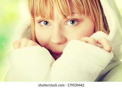 Beautiful young caucasian woman in bathrobe after bath calm portrait,  on abstract green background