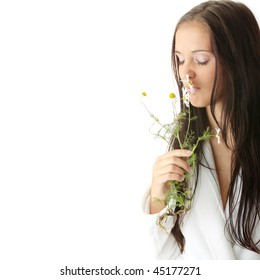 Beautiful young caucasian woman in bathrobe smeling daisy calm portrait. Isolated
