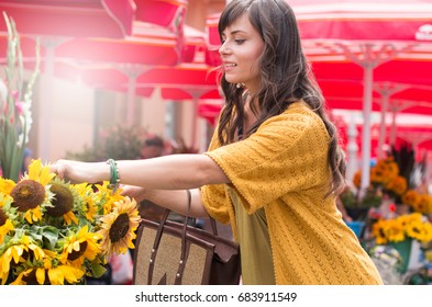 beautiful young caucasian woman buying flowers on the local market