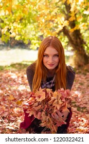 A beautiful young Caucasian woman holding lot of leaves in her hands in a park. Conceptual image for autumn and beauty.